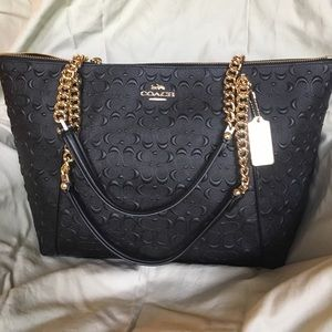 Large embossed black Coach tote with gold chains